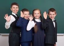 Ragazzo della scuola elementare vicino al fondo in bianco della lavagna, vestito in vestito nero classico, allievo del gruppo, co Immagini Stock