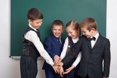 Ragazzo della scuola elementare vicino al fondo in bianco della lavagna, vestito in vestito nero classico, allievo del gruppo, co Fotografie Stock