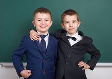 Ragazzo della scuola elementare vicino al fondo in bianco della lavagna, vestito in vestito nero classico, allievo del gruppo, co Immagine Stock