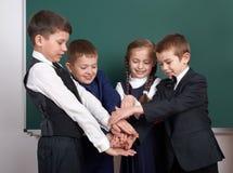 Ragazzo della scuola elementare vicino al fondo in bianco della lavagna, vestito in vestito nero classico, allievo del gruppo, co Fotografia Stock