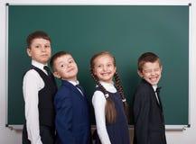 Ragazzo della scuola elementare vicino al fondo in bianco della lavagna, vestito in vestito nero classico, allievo del gruppo, co Immagine Stock Libera da Diritti