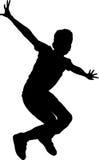 Ragazzo della siluetta del salto Fotografie Stock