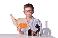 Ragazzo dello scienziato in vetri allo scrittorio con un libro in sua mano Immagine Stock Libera da Diritti