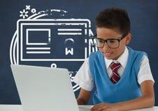 Ragazzo dello studente alla tavola che esamina un computer contro la lavagna blu con la scuola ed il grafico di istruzione Immagine Stock Libera da Diritti