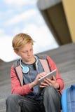 Ragazzo dello studente che per mezzo della compressa che si siede sui punti Immagini Stock Libere da Diritti
