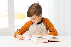 Ragazzo dello studente con il libro che scrive al taccuino a casa Fotografia Stock Libera da Diritti