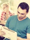Ragazzo dello studente con la compressa davanti ai suoi compagni di classe Fotografia Stock