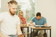 Ragazzo dello studente con la compressa davanti ai suoi compagni di classe Immagini Stock Libere da Diritti