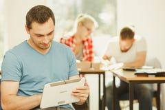 Ragazzo dello studente con la compressa davanti ai suoi compagni di classe Fotografie Stock Libere da Diritti