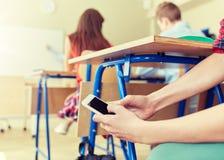 Ragazzo dello studente con lo smartphone che manda un sms alla scuola Fotografia Stock