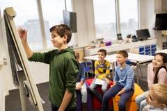Ragazzo dello studente con scrittura dell'indicatore sul bordo di vibrazione Immagine Stock Libera da Diritti