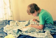 Ragazzo di 7 anni che gioca con un computer portatile Fotografia Stock Libera da Diritti