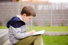 Ragazzo di 7 anni che legge un libro sul terrazzo Fotografie Stock