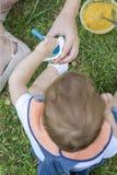 Ragazzo di 2 anni che mangia un yogurt che si siede sull'erba Immagine Stock Libera da Diritti