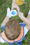 Ragazzo di 2 anni che mangia un yogurt che si siede sull'erba Immagine Stock