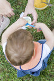 Ragazzo di 2 anni che mangia un yogurt che si siede sull'erba Fotografia Stock