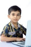 Ragazzo di banco che per mezzo di un computer portatile Fotografia Stock Libera da Diritti