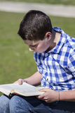 Ragazzo di Childhood.Young che legge un libro nel legno con il reparto basso Fotografia Stock