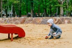 Ragazzo di cinque anni che gioca nella sabbia fotografia stock