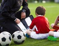 Ragazzo di Coaching Preschool Soccer della vettura Vettura Explaining Tactics Basics della gioventù di calcio sul bordo di tattic fotografia stock