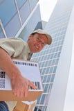 Ragazzo di consegna che sta in Front Of Modern Buildings Fotografie Stock Libere da Diritti