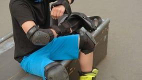 Ragazzo di formazione di protezione di sport che mette il cuscinetto di polso stock footage