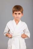 Ragazzo di karatè nel combattimento bianco del kimono Fotografie Stock Libere da Diritti