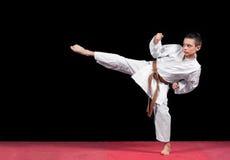 Ragazzo di karatè nel combattimento bianco del kimono isolato su fondo nero Fotografia Stock