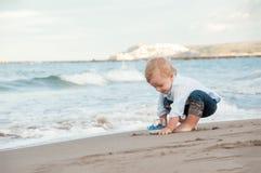 Ragazzo di Litlle che gioca sulla spiaggia con una nave Vacanze estive e Fotografia Stock Libera da Diritti