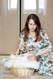 Ragazzo di neonato che si trova in un canestro, mamma che segna un neonato Immagini Stock Libere da Diritti