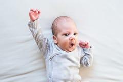 Ragazzo di neonato sveglio che si trova sul letto, fine su immagini stock