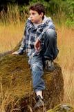 Ragazzo di paese del Preteen che si siede su una roccia Fotografia Stock