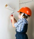Ragazzo di quattro anni nel painstakingl protettivo della costruzione del casco Fotografie Stock