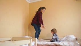 Ragazzo di risata allegro del bambino che esamina sorella più anziana che salta sul letto video d archivio