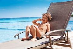 Ragazzo di risata che mette sulla chaise-lounge del sole e che prende il sole Fotografia Stock