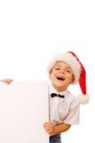 Ragazzo di risata con il cappello della Santa ed il segno in bianco Immagine Stock