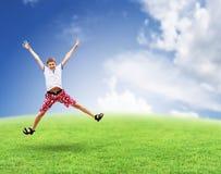 Ragazzo di salto sull'erba. Cielo. fotografia stock libera da diritti