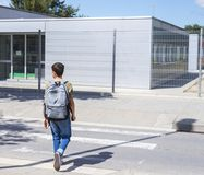 Ragazzo di scuola adolescente con uno zaino sul suo parte posteriore che cammina alla scuola Fotografia Stock