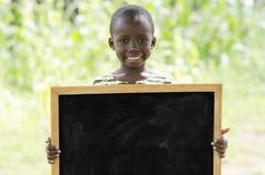 Ragazzo di scuola africano che posa sotto il sole con un grande spazio della copia della lavagna Fotografie Stock Libere da Diritti
