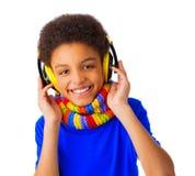 Ragazzo di scuola afroamericano che ascolta la musica con la cuffia avricolare Fotografie Stock Libere da Diritti