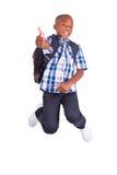 Ragazzo di scuola afroamericano che salta e che compone il nero dei pollici - Immagini Stock