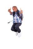 Ragazzo di scuola afroamericano che salta e che compone il nero dei pollici - Fotografie Stock