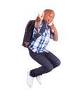 Ragazzo di scuola afroamericano che salta e che compone il nero dei pollici - Immagini Stock Libere da Diritti