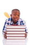 Ragazzo di scuola afroamericano con la pila un libro - persone di colore Immagine Stock