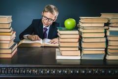 Ragazzo di scuola astuto che legge un libro alla biblioteca Immagini Stock