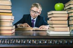Ragazzo di scuola astuto che legge un libro alla biblioteca Fotografie Stock