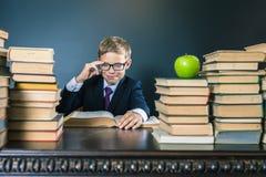 Ragazzo di scuola astuto che legge un libro alla biblioteca Fotografia Stock
