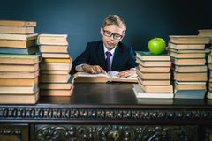 Ragazzo di scuola astuto che legge un libro alla biblioteca Immagini Stock Libere da Diritti
