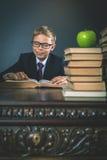 Ragazzo di scuola astuto che legge un libro alla biblioteca Fotografie Stock Libere da Diritti