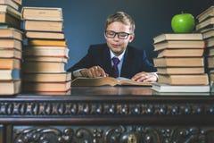 Ragazzo di scuola astuto che legge un libro alla biblioteca Immagine Stock